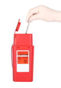 A hand putting a syringe into a sharps medical waste container.